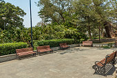 Wide view of group of unoccupied wooden seats or chairs arranged in a garden or park, Chennai, India