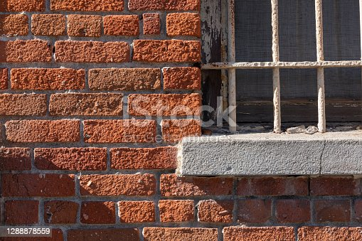 A horizontal close-up image of an old, white, barred window, with morning shadows, set into an orange brick wall.