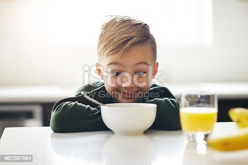 Cropped shot of an adorable little boy having breakfast while sitting in the kitchen