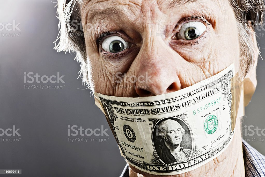 Wide-eyed angry old woman with dollar bill gag stock photo