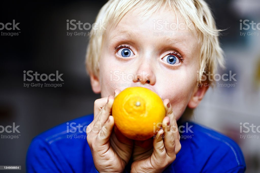 Wide-eyed boy squeezes juicy citrus, yum! stock photo