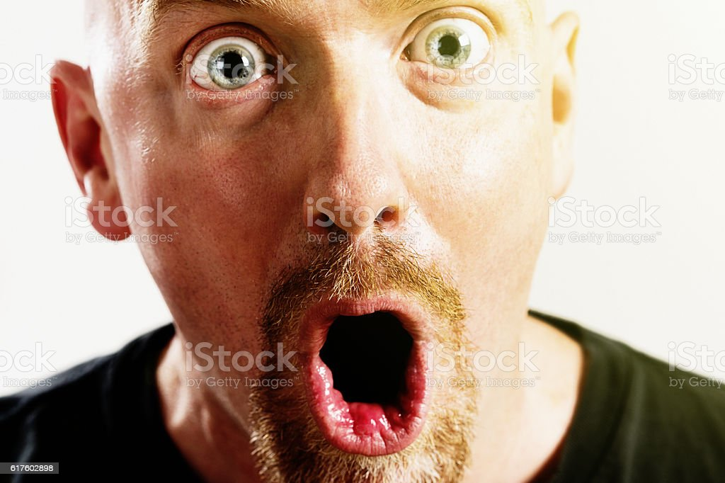 Wide-eyed man gasps in amazed disbelief stock photo