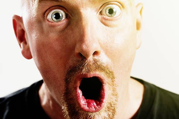 wide-eyed man gasps in amazed disbelief - haarschnitt rundes gesicht stock-fotos und bilder