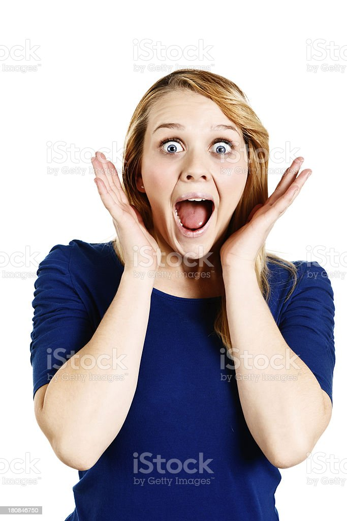 Wide-eyed pretty blonde gasps in amazement, hands to her head royalty-free stock photo
