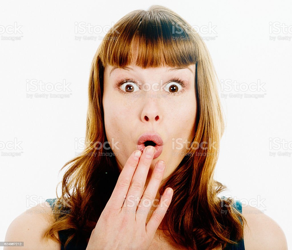 Wide-eyed red-headed beauty looks playfully surprised stock photo