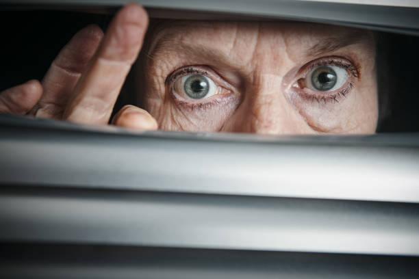 Wide-eyed senior woman peeping nervously through blinds stock photo
