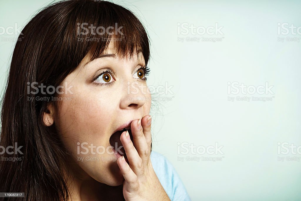 Wide-eyed, shocked young woman, hand over mouth royalty-free stock photo