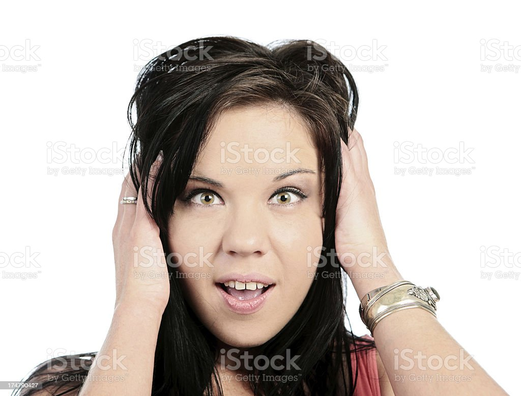 Wide-eyed, surprised brunette with hands to her head royalty-free stock photo