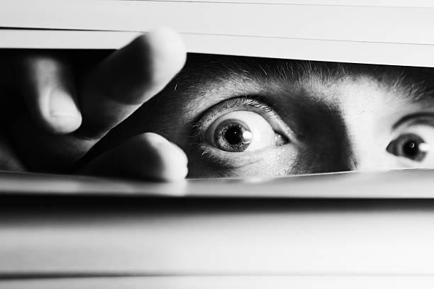 Wide-eyed terrified man peeping though venetian blinds stock photo