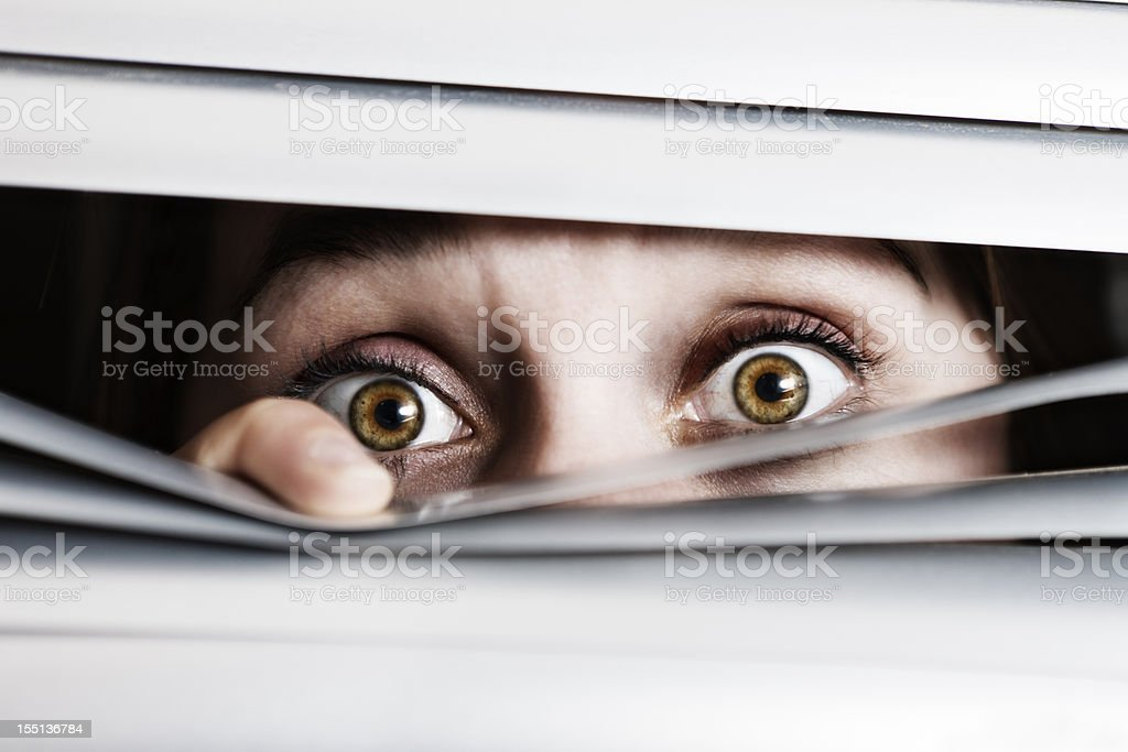 Wide-eyed, terrified young woman looks out through venetian blinds stock photo
