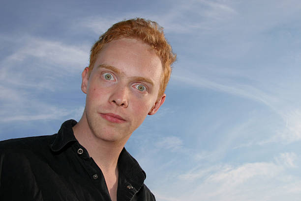 Wide-eyed young man against blue sky stock photo