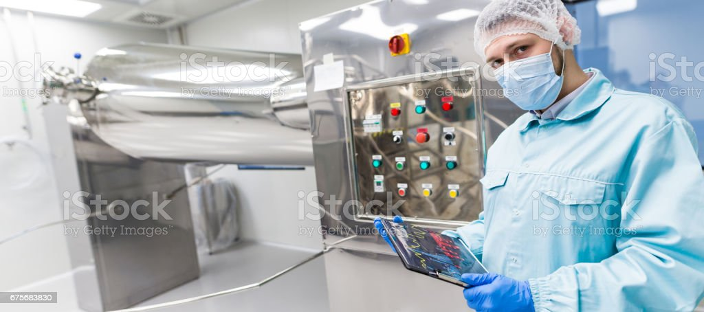 widescreen picture, factory worker is checking control panel on machine, close royalty-free stock photo