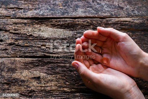 istock widow holding her husband's ring on a wooden background 542000932