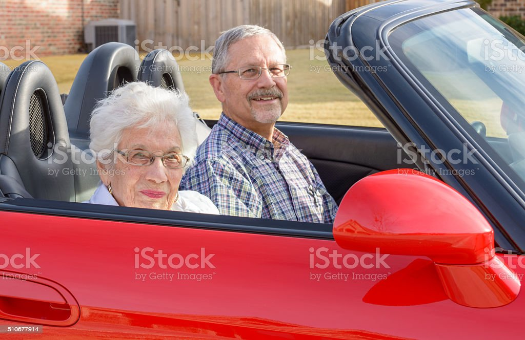 Widow mother rides with boomer son in red sports car stock photo