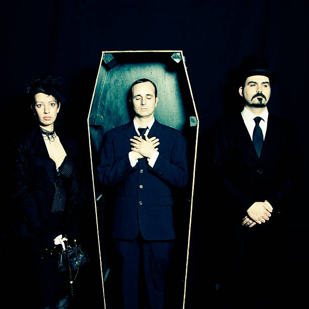 Widow, undertaker and man in coffin stock photo