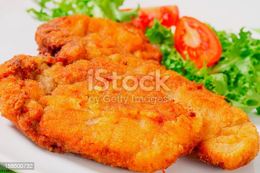 big fried breaded Wiener schnitzel (escalope) with vegetable garnish on a white plate