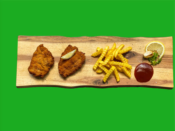 Wiener Schnitzel with french fries on a wooden plate, green background, green screen stock photo