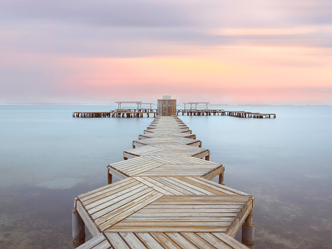 Wiew of a wooden pier in Mar Menor lagoon, from Los Alcazares, Murcia, Spain at dawn. A long boardwalk on the calm water of the lake at dusk.