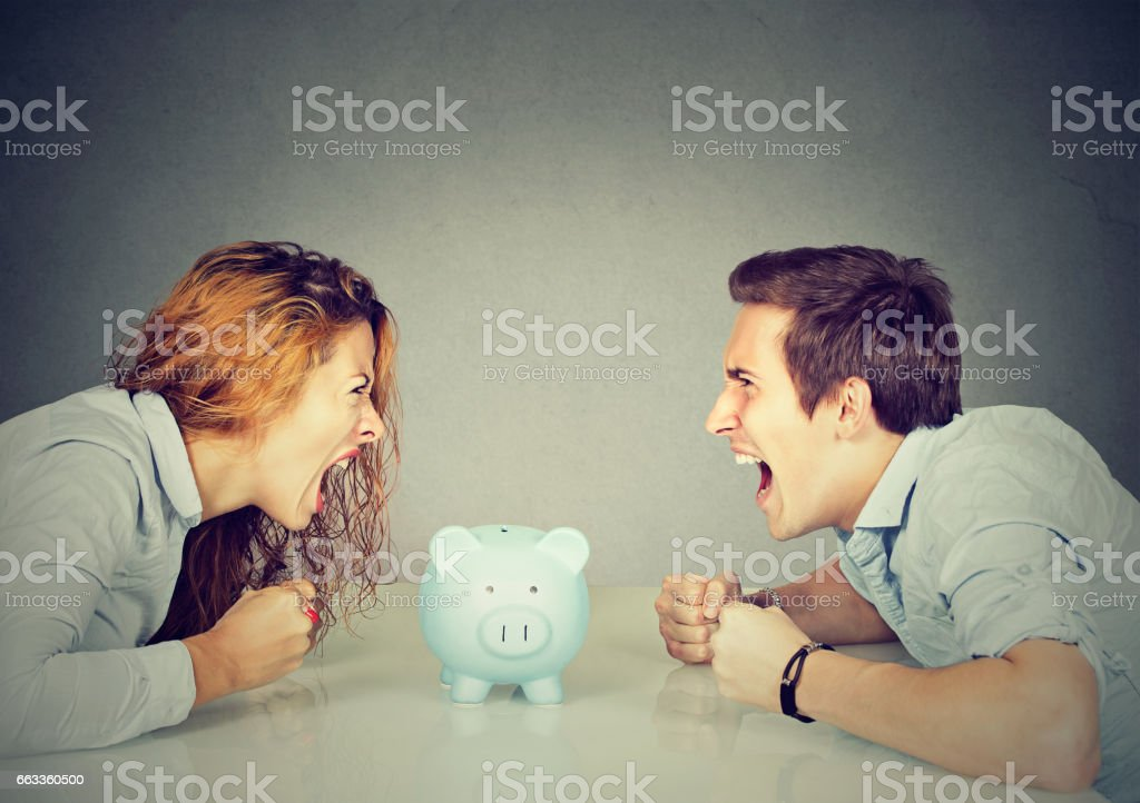 Wife and husband can not make settlement screaming piggy bank in-between stock photo