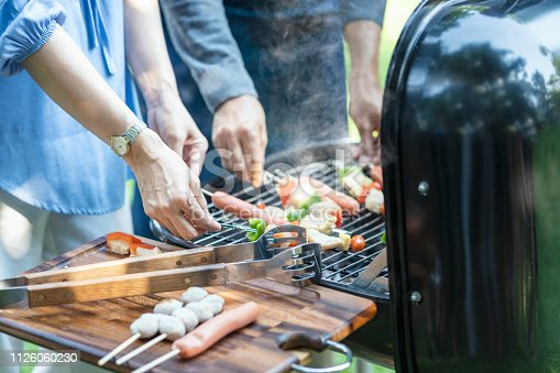696841580istockphoto Wife and husband making grilled meat bbq with sausage over the coals on barbecue. 1126060230