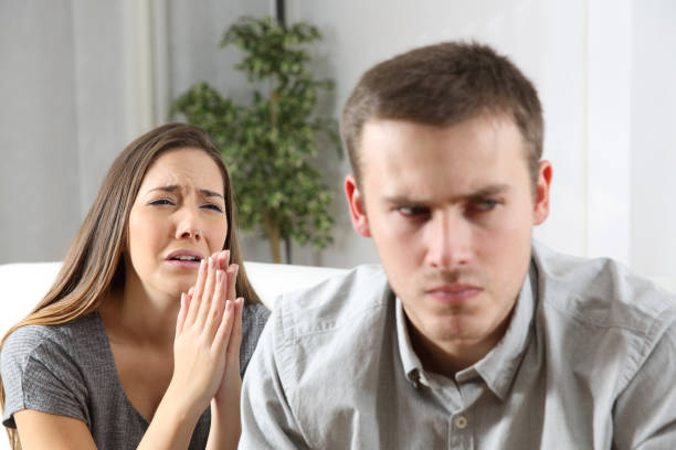 Wife asking for forgiveness to her husband stock photo