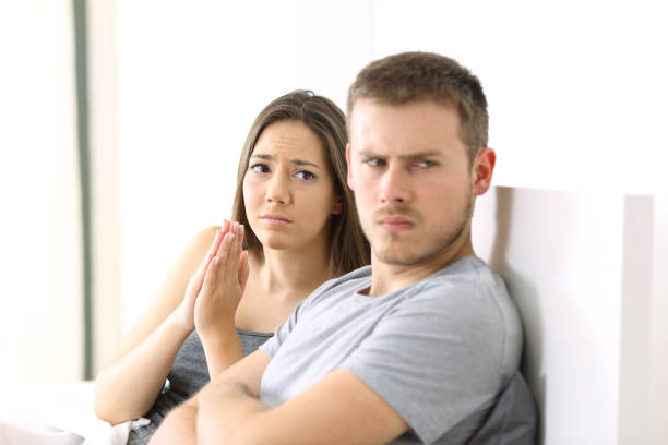 Wife begging and angry husband Wife begging to her angry husband sitting on the bed in a house interior pleading stock pictures, royalty-free photos & images