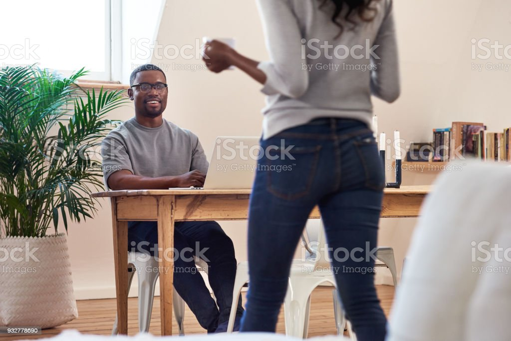 Wife bringing her husband a cup of coffee while he works from home stock photo