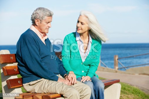 874789476istockphoto Wife comforting her depressed husband on a seaside bench 177752064