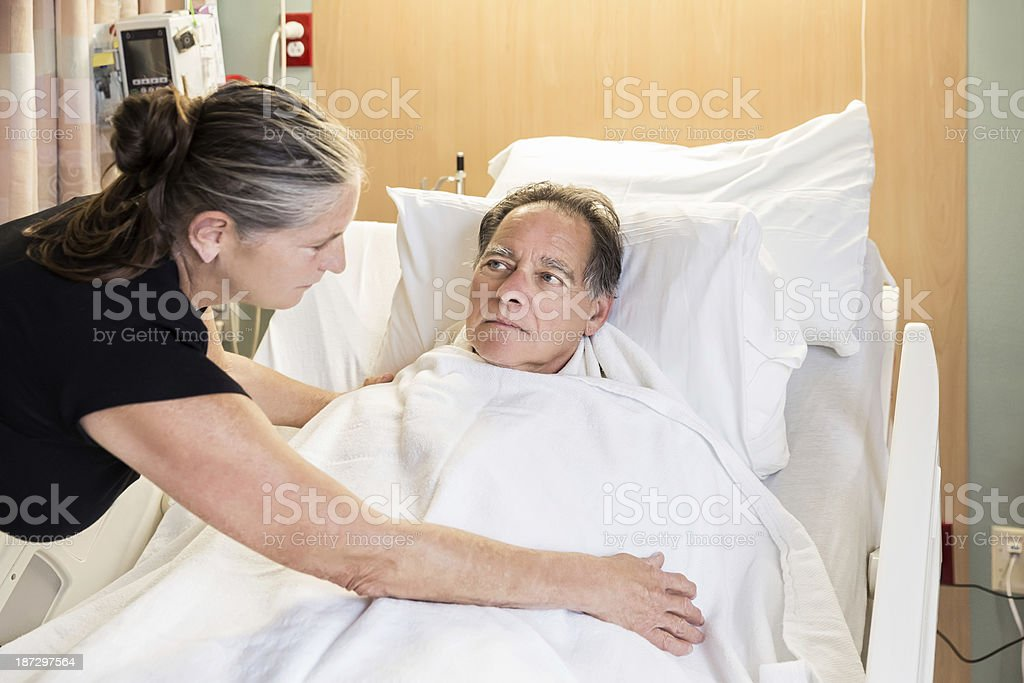 A wife covering up her husband who is in hospital bed. royalty-free stock photo