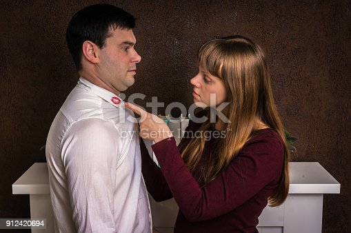 185866319istockphoto Wife finded red lipstick on shirt collar - infidelity concept 912420694