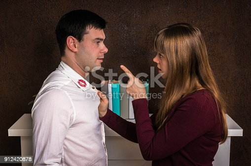 185866319istockphoto Wife finded red lipstick on shirt collar - infidelity concept 912420878