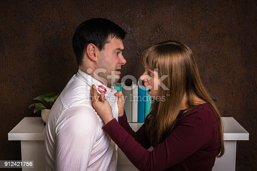 185866319istockphoto Wife finded red lipstick on shirt collar - infidelity concept 912421756