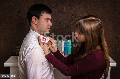 185866319istockphoto Wife finded red lipstick on shirt collar - infidelity concept 912421868