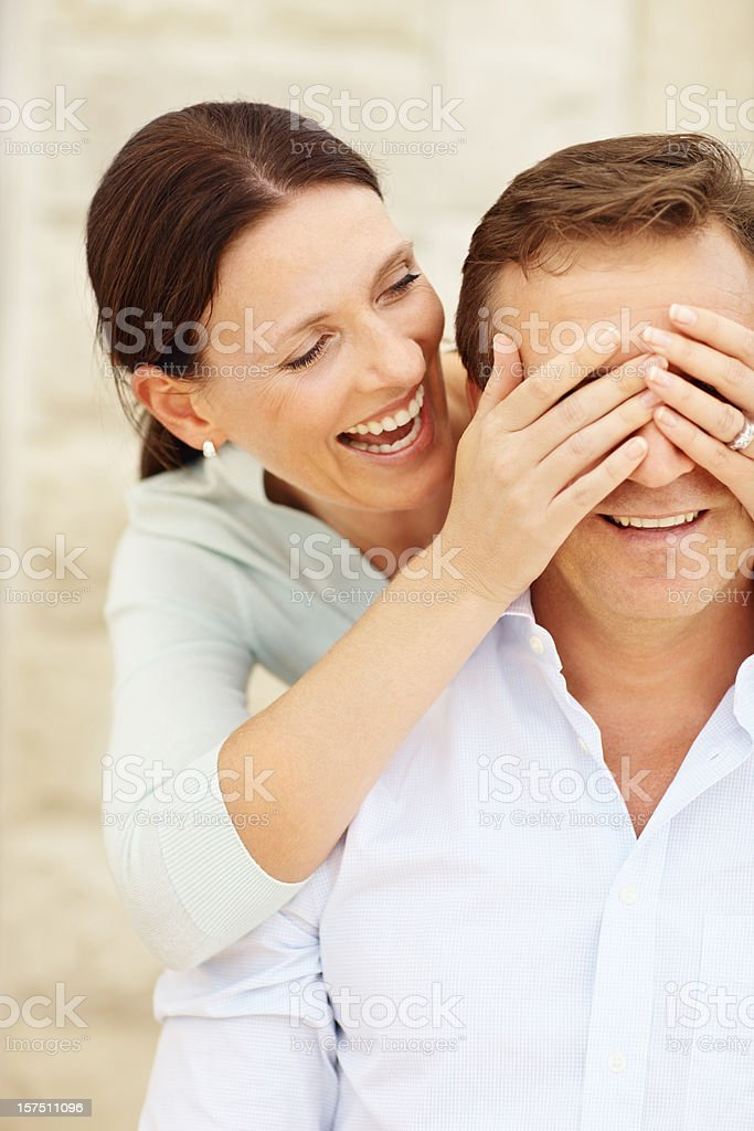Wife giving surprise to her husband's royalty-free stock photo