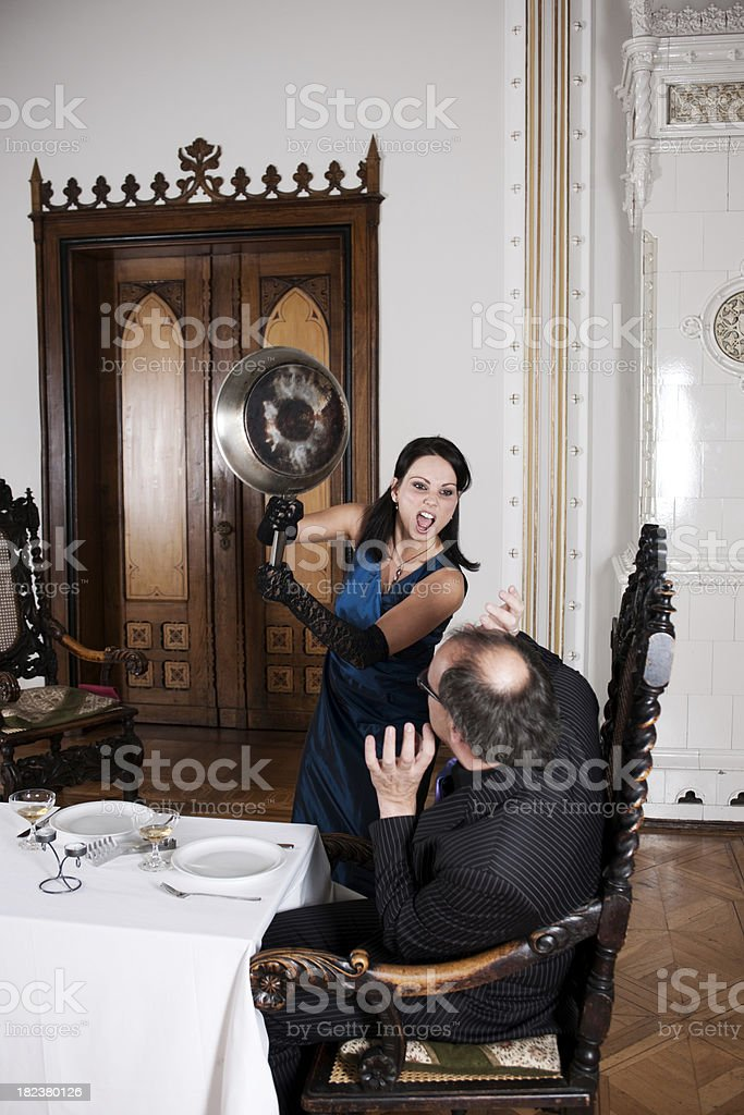 Wife is threatening her husband with a pan royalty-free stock photo