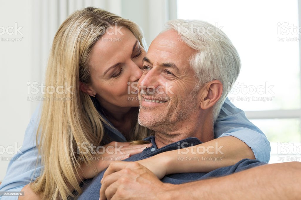 Wife kissing husband stock photo