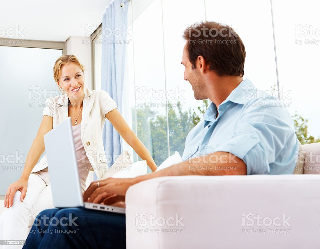Wife looking at her husband working on a laptop royalty-free stock photo