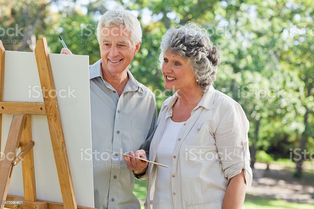 wife looks at her husbands painting on canvas royalty-free stock photo