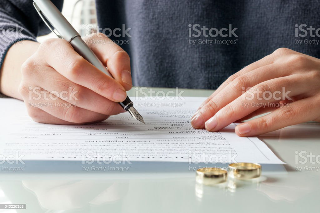 Wife signs divorce decree form with ring stock photo