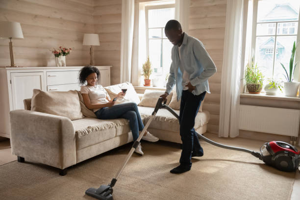 Wife sitting on couch while husband vacuum carpet stock photo