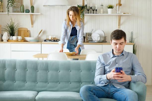 Frau nimmt Geschirr Mann sitzt auf Sofa mit Telefon – Foto