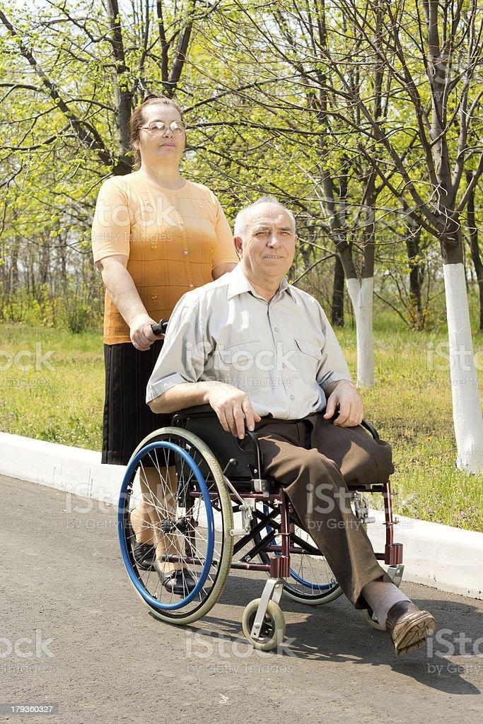 Frau, die Ihren Behinderten Mann für einen Spaziergang – Foto