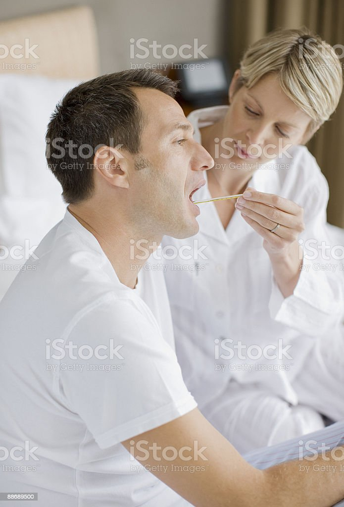 Wife taking husbands temperature royalty-free stock photo