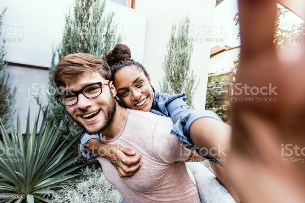 Wife taking selfie of her and her husband, piggy back ride stock photo
