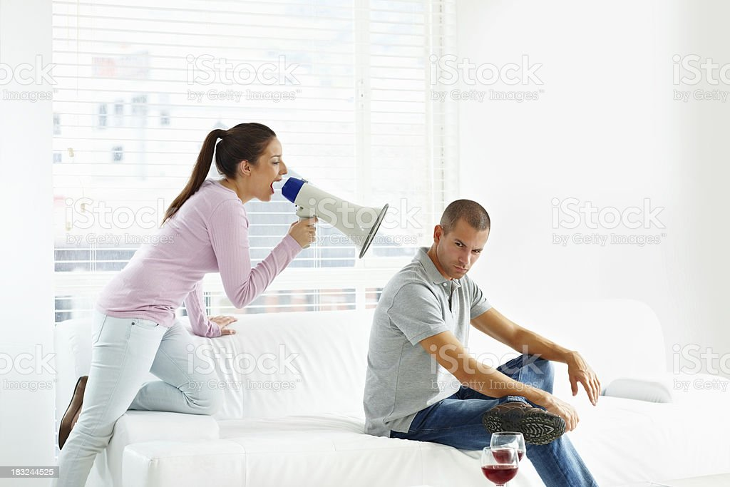 Wife using a megaphone to scream at her husband royalty-free stock photo