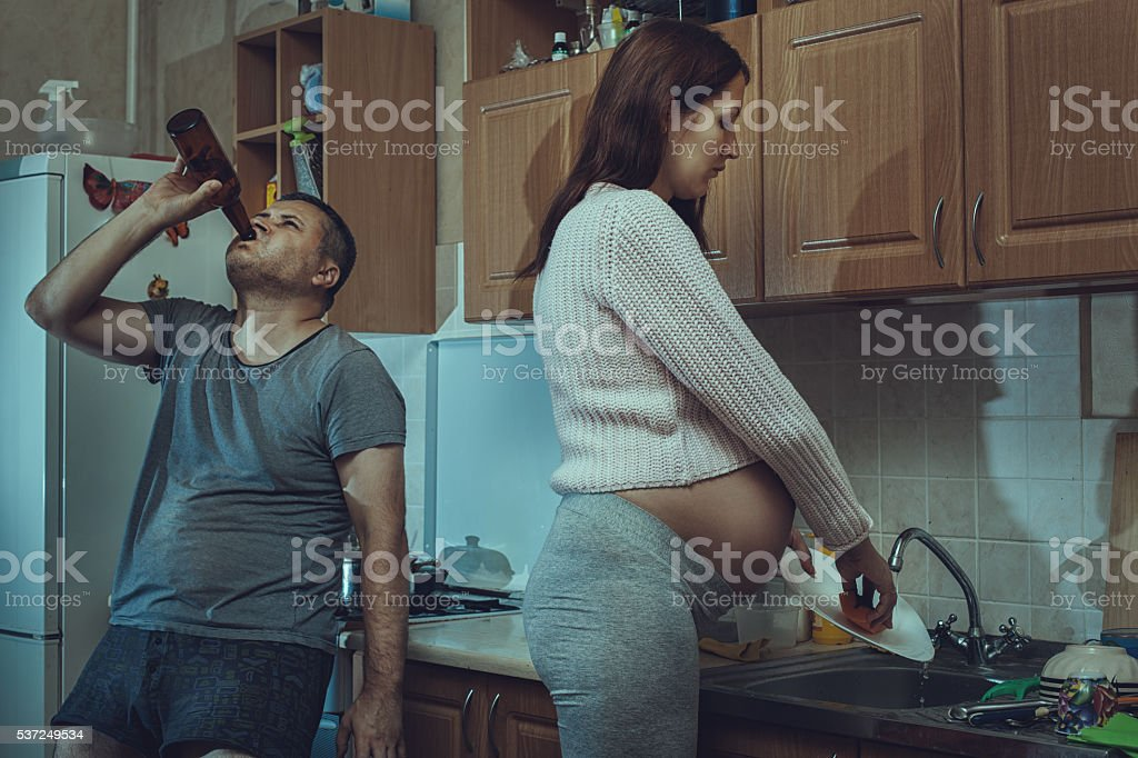 Wife washes the dishes, alcoholic husband. stock photo