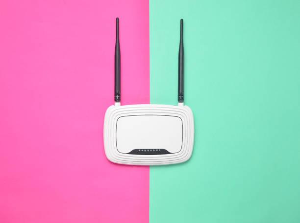 wlan-router auf einem farbigen hintergrund pastell. trend des minimalismus. immer online. ansicht von oben. - router stock-fotos und bilder