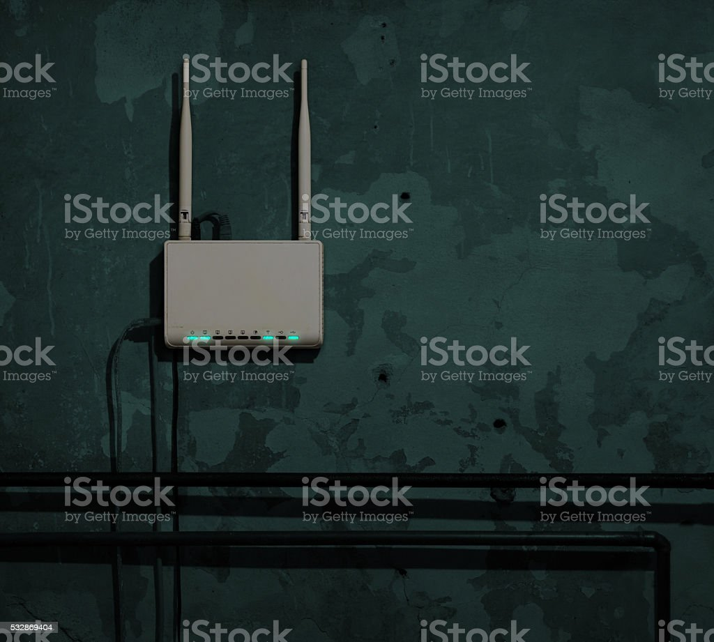 Wi-Fi router on an old wall in a dark room stock photo