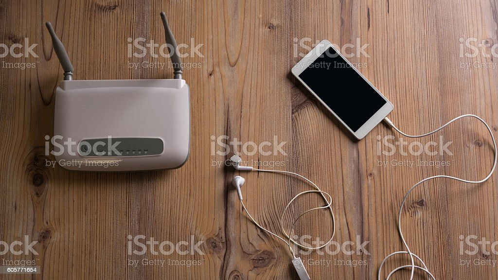 Wi-Fi wireless router and phone on the floor stock photo