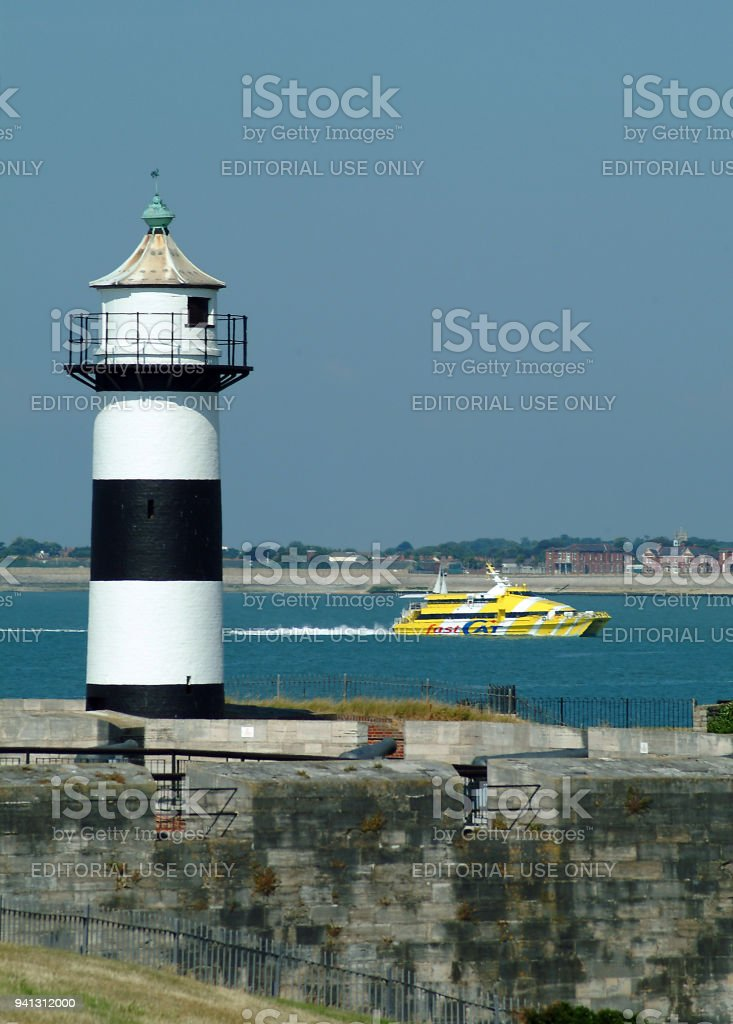 A Wightlink FastCat ferry passes the Portsmouth Harbour lighthouse on it's way to the Isle of Wight. stock photo